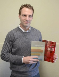 Professor Accardi holding the two books his class published