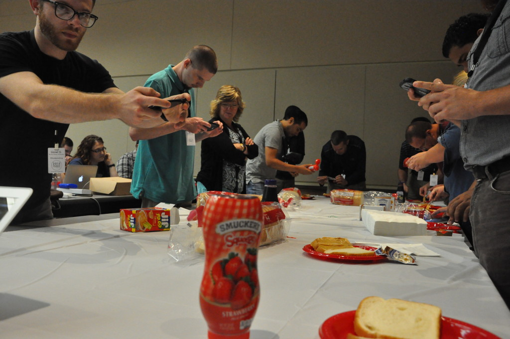 People making peanut butter and jelly sandwiches at table with Smuckers jelly container in foreground.