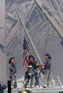 NEW YORK - SEPTEMBER 11: (EDITORIAL USE ONLY - NO COMMERCIAL SALES) Firefighters raise a U.S. flag at the site of the World Trade Center after two hijacked commercial airliners were flown into the buildings September 11, 2001 in New York.  (Photo by 2001 The Record (Bergen Co. NJ)/Getty Images)
