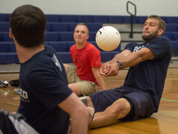 Max Rohn sets the ball during a game of seated volleyball.