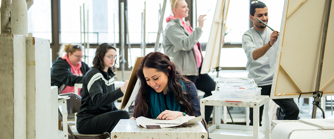 Students work at easels in an art studio.