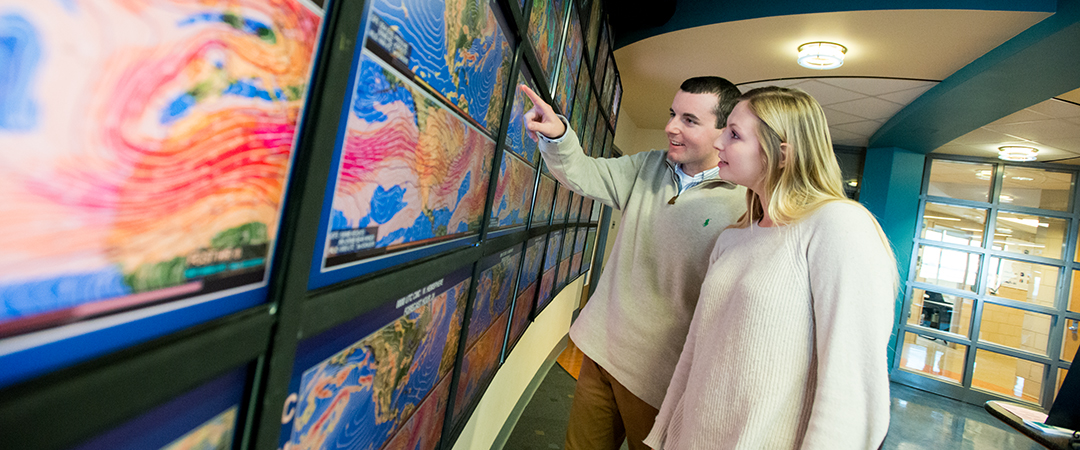 Ryan Breton, a junior studying Meteorology, shows another student an image on a video screen inside the Joel N. Myers Weather Center in Walker Building.