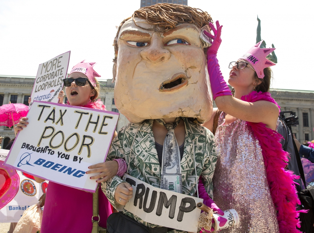"Protester Chelsea Byers, right, of Los Angeles, pretends to use money to wipe sweat from the brow of a giant Donald Trump head worn by Alice Newberry of Washington State. They are joined by Rebecca Green, left, of Cleveland. The women, members of ""Code Pink,"" marched with other protesters through Public Square in Cleveland on Monday, July 18, 2016 during the Republican National Convention. / Photo by Antonella Crescimbeni"