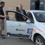 Penn State President Eric Barron hops into the EcoCAR competition vehicle. The team chauffeured Barron back to Old Main for his next appointment of the day.
