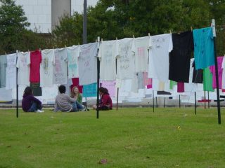 Students studying among the Campus Clothesline Project.
