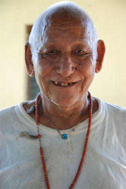 Smiling elderly man with beaded necklace.